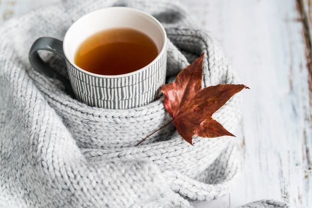 Taza con té en bufanda tejida con hoja de arce