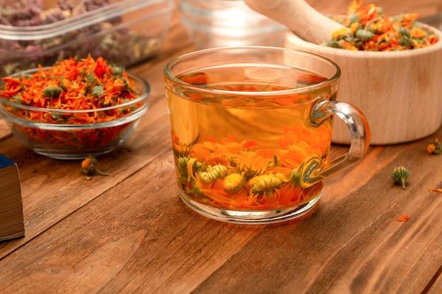 Taza de té de caléndula seca sobre una mesa de madera.