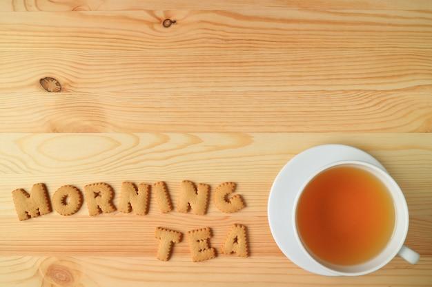 Taza de té caliente al lado con la palabra té de mañana ortografía con galletas galletas en la mesa de madera