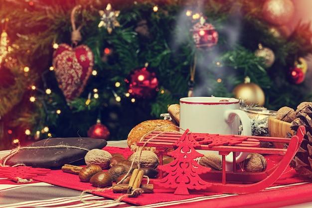 Taza de té caliente con detrás de árbol de navidad.