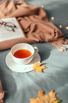 Taza de té caliente con hojas de otoño y decoración de guirnaldas de luz, libro y vasos en cuadros grises en la cama