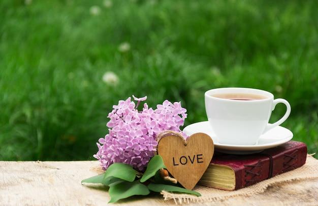 Taza de té caliente, libro y lilas sobre fondo de hierba verde
