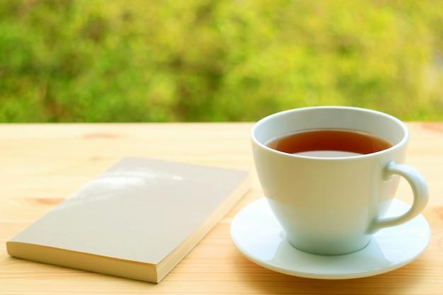 Taza de té caliente y un libro sobre una mesa al aire libre con follaje borroso en segundo plano.