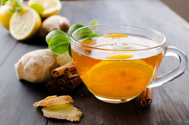 Taza de té caliente con limón y jengibre.