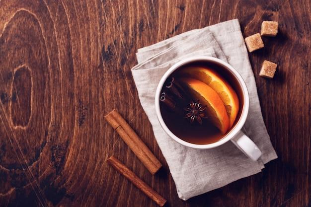 Taza de té caliente con naranja y especias sobre una rústica mesa marrón. de cerca