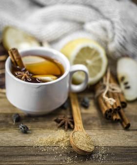 Taza de té caliente con palitos de canela y limón