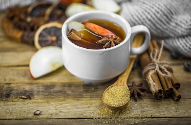 Una taza de té caliente con una rama de canela y una cucharada de azúcar morena sobre madera