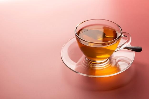 Una taza de té caliente recién hecho en un vaso sobre el fondo rosa con espacio de copia