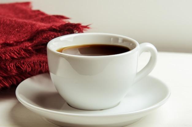 Taza con té caliente sobre una mesa blanca con una manta roja doblada.