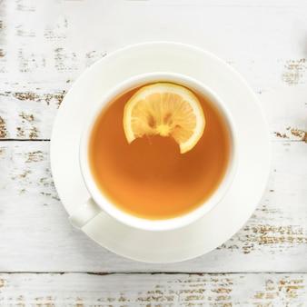 Taza de té caliente en superficie de madera