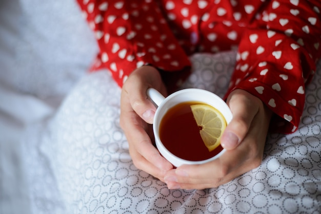 Taza de té caliente con un trozo de limón en manos de una niña solitaria en la mañana