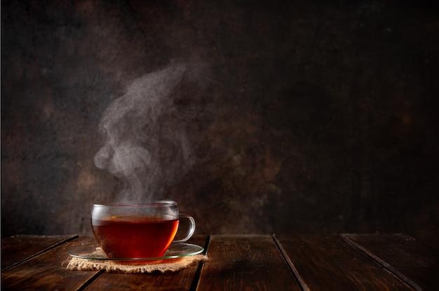 Taza de té caliente con vapor a oscuras