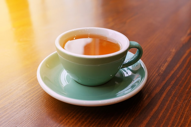 Una taza de té caliente y vigorizante en una mesa de madera, té de la mañana. enfoque selectivo. la foto se superpone con grano y ruido.