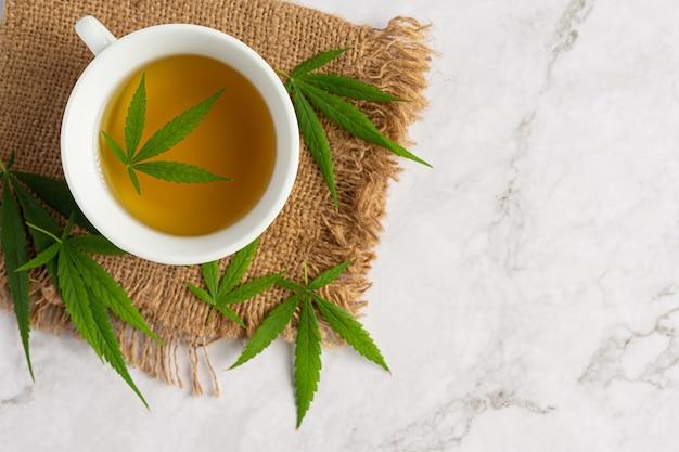 Taza de té de cáñamo con hojas de cáñamo en suelo de mármol blanco