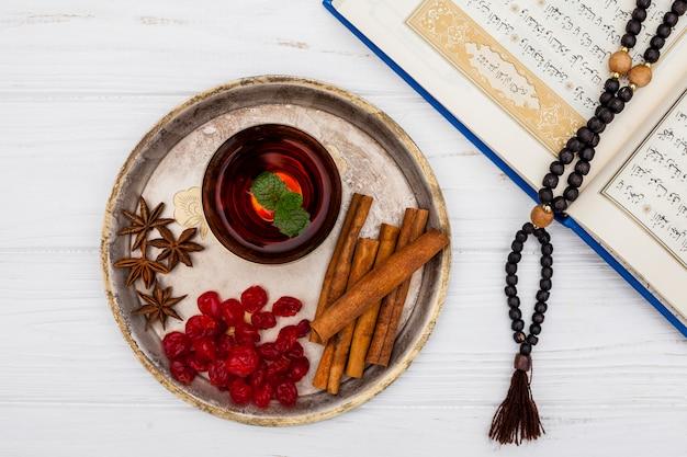 Taza de té con canela y corán sobre mesa