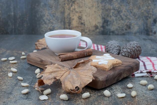 Taza de té, canela y galletas de jengibre en placa de madera. foto de alta calidad