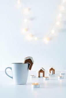 Taza de té con casa de pan de jengibre y velas sobre fondo blanco. luces de navidad. marco vertical.