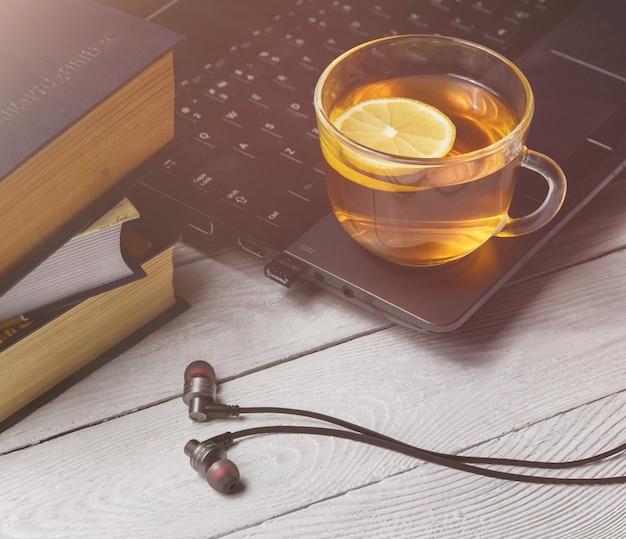 Taza de té en la computadora portátil y el libro.