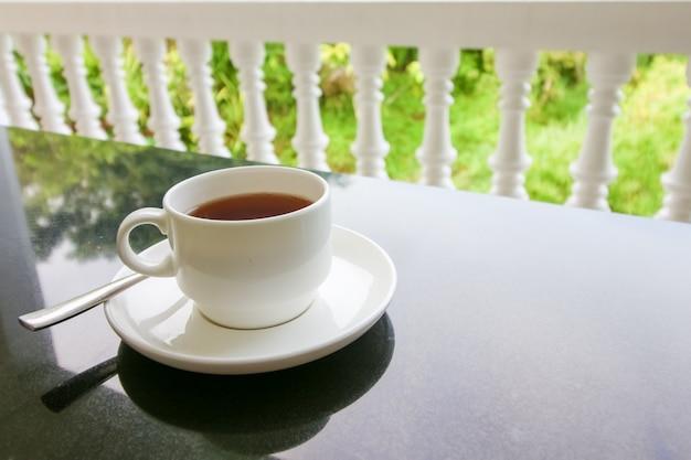 Taza del té con cuchara y plato sobre la mesa negra.