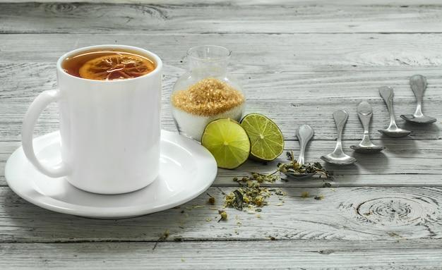 Taza de té y cucharas en una hermosa pared de madera blanca, invierno, otoño