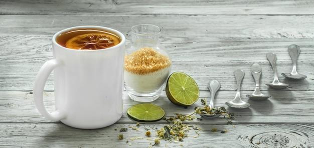 Taza de té y cucharas sobre un hermoso fondo de madera blanca, invierno, otoño