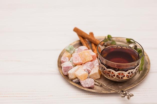 Taza de té con delicias turcas en plato sobre mesa