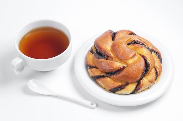 Taza de té y delicioso bollo con crema de chocolate sobre fondo blanco.