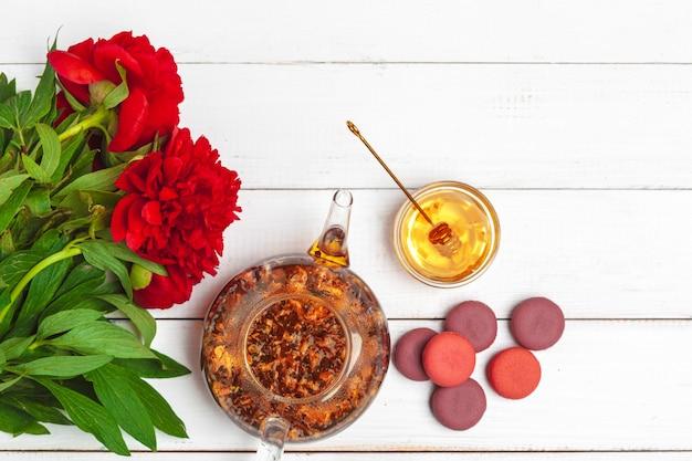 Taza de té con dulces y flores en la mesa de madera