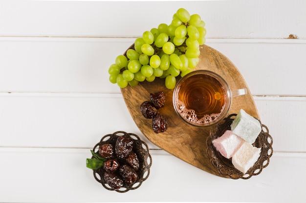 Taza de té con dulces orientales y uvas.