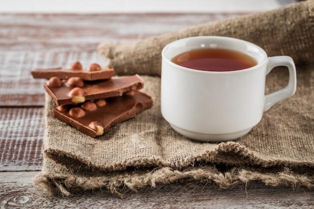 Una taza de té es chocolate negro sobre la madera.