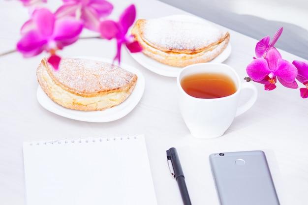 Taza de té, flores, bloc de notas en espiral, bolígrafo. gestión del tiempo, nuevo concepto de planificación del día.