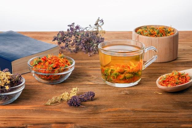 Una taza de té de flores de caléndula en una mesa de madera con una colección de hierbas medicinales secas.