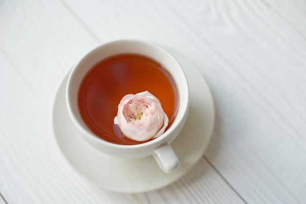 Taza de té con flores frescas sobre un fondo blanco. vista desde arriba. espacio para copia.