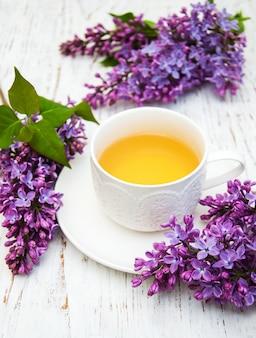 Taza de té y flores lilas.