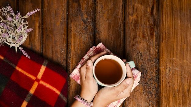 Taza de té, flores y manta de invierno en madera vieja