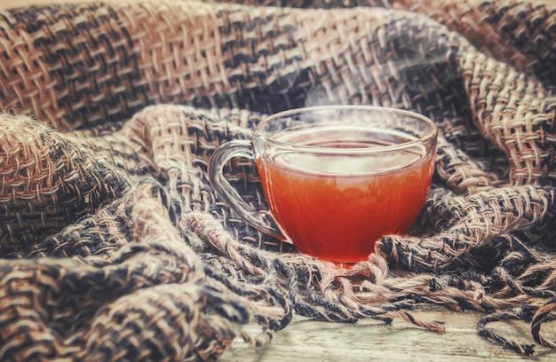 Una taza de té y un fondo acogedor de otoño. enfoque selectivo