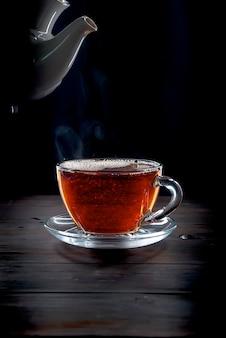 Taza de té en el fondo negro