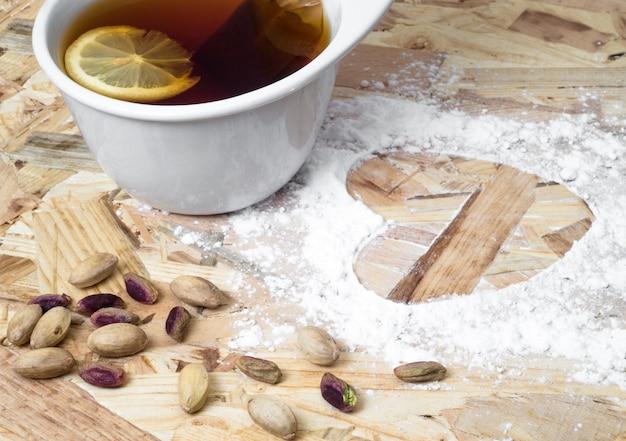 Taza de té con forma de corazón en la mesa de madera