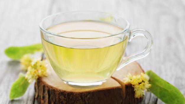 Taza de té fresco hecho con hojas de tilo sobre un soporte de madera