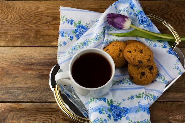 Taza de té y galletas en la bandeja de servir