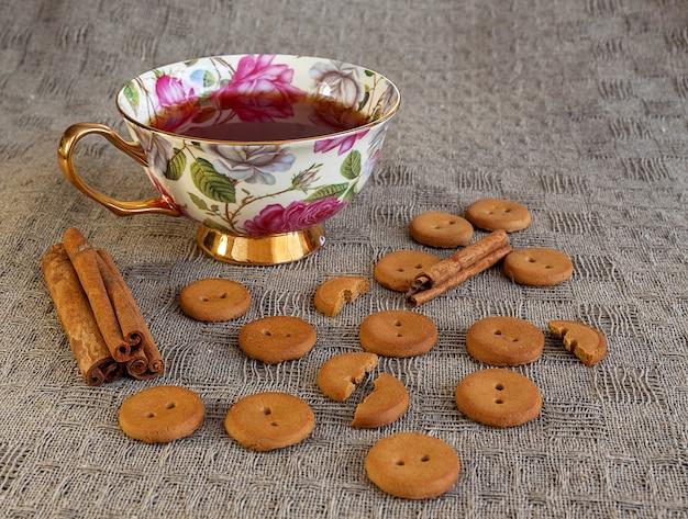 Taza de té con galletas y canela en la mesa