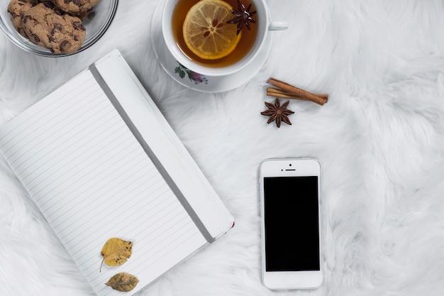 Taza de té con galletas cerca de bloc de notas y teléfono inteligente