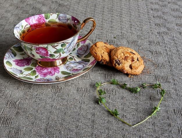 Taza de té con galletas y corazón de tomillo