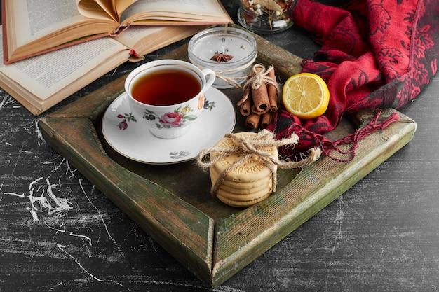 Una taza de té con galletas y frutas.