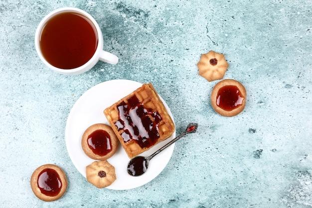 Una taza de té, galletas y gofres con mermelada de fresa.