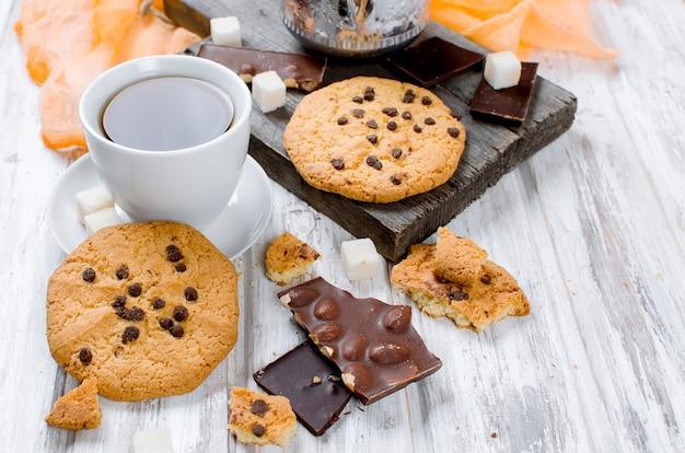 Taza de té, galletas en la mesa de madera blanca