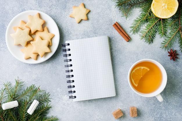 Taza de té y galletas, ramas de pino, ramas de canela, estrellas de anís