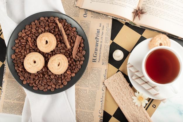 Una taza de té y granos de café con galletas.