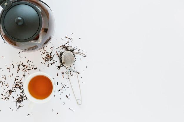Taza de té con hervidor de agua y colador