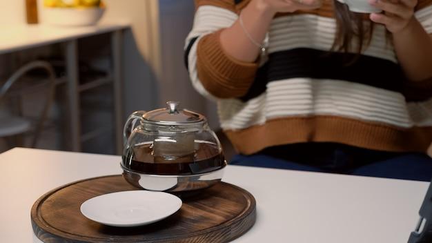 Taza de té y hervidor de agua sentado en la mesa de la cocina blanca